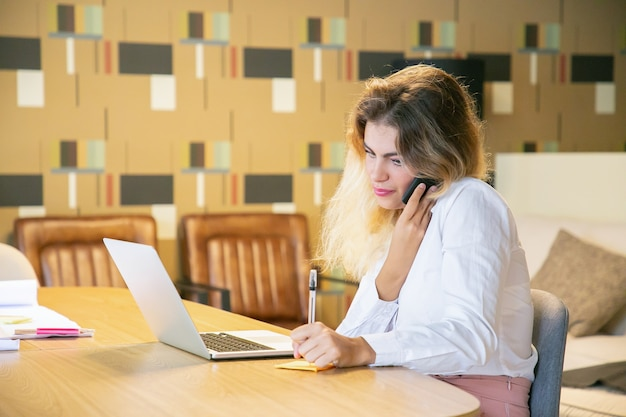 Libero professionista concentrato che discute progetto con il cliente sul telefono