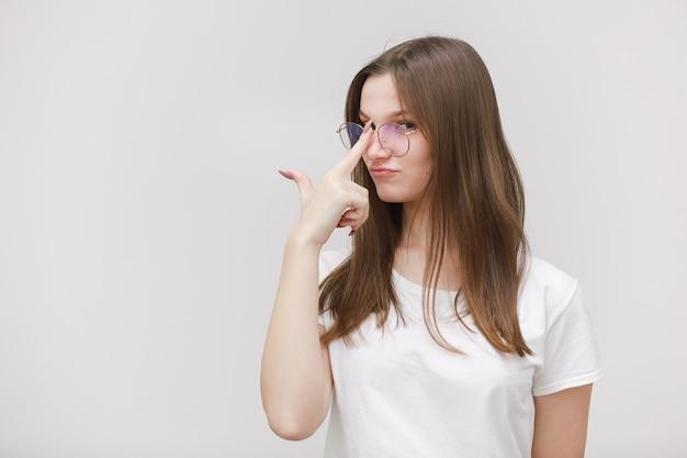 Сосредоточенные хмурится офисная девушка, глядя на камеру через очки на белом фоне. молодая женщина, регулируя очки. концепция ношения очков.