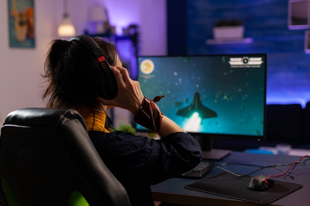 Focused gamer는 전문 헤드폰을 사용하고 공간 사수 비디오 게임은 디지털 토너먼트를 위해 최신 장비를 사용합니다. rgb 키워드를 사용하여 비디오 게임을 스트리밍하는 게임용 의자에 앉아 있는 프로 플레이어