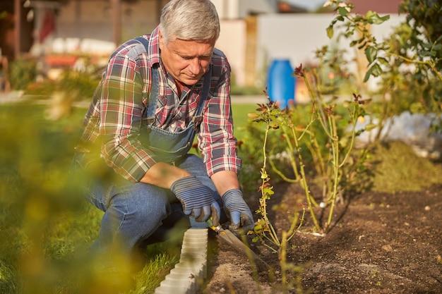 집중 정원사는 화단 근처에 쪼그리고 앉아 흙을 파면서 흙손을 들고 있다