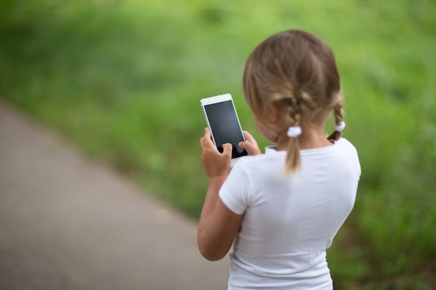 Focused girl child with smartphone, outdoors,