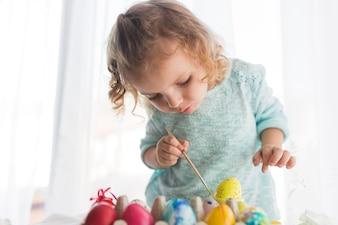 Focused girl coloring egg for Easter