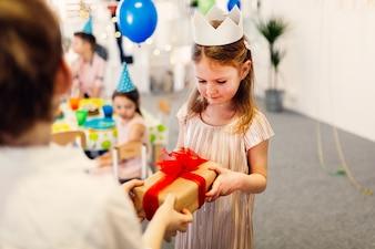 Focused girl in white crown taking gift