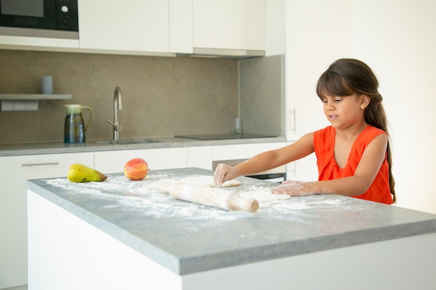 부엌 테이블에서 반죽을 반죽하는 집중된 소녀. 혼자서 빵이나 케이크를 굽는 아이. 미디엄 샷. 가족 요리 개념