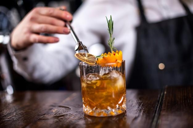 バーの後ろのグラスに新鮮なアルコール飲料を注ぐ焦点を絞った女の子のミクソロジスト