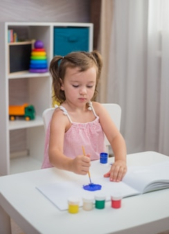 A focused girl paints in an album with a brush and paints in the children's room