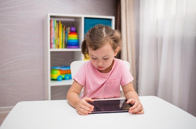 Сосредоточенная девушка играет с планшетом за столом в комнате