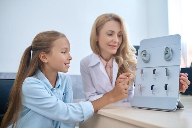医師の助けを借りて補聴器を選択する焦点を絞った女の子