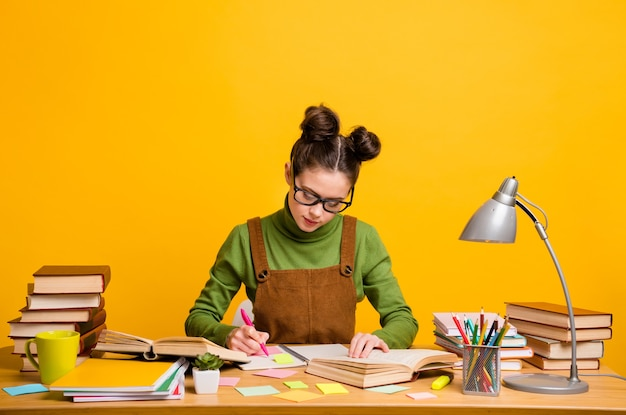 Focused girl sit table write copybook over yellow color background
