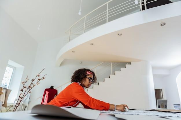 집중된 잘 생긴 재봉사. 넓은 스튜디오에서 작업하는 동안 그녀의 귀에 hoopla 농구를 착용하는 곱슬 여성 디자이너