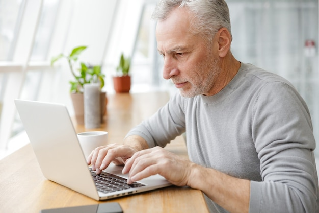 Focused gray-haired man typing on laptop and drinking coffee while sitting in cafe indoors
