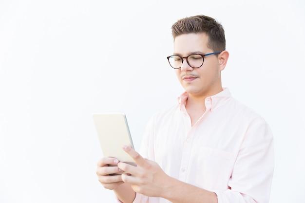 Focused guy in eyeglasses reading on tablet screen