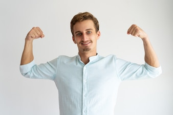 Focused guy in white casual shirt showing strength gesture.