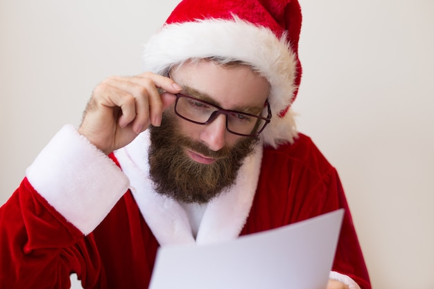 Focused guy wearing santa costume and reading document