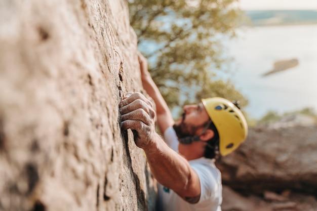 일몰에 암벽 등반을 하는 30대 남자의 집중된 손