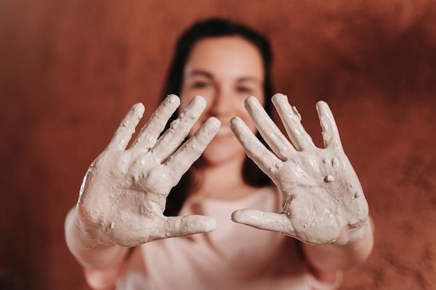 테라코타라는 재료로 채워진 여성의 집중된 손 프리미엄 사진