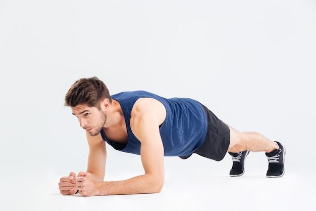 Сосредоточенный красивый молодой спортсмен делает базовые упражнения планки на белом фоне