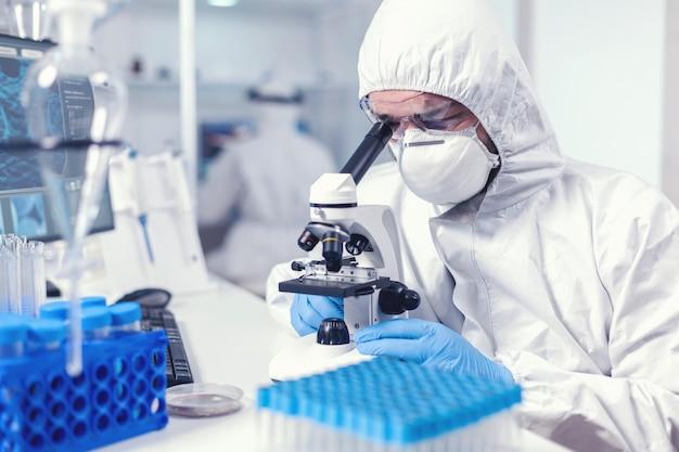 Сосредоточенный исследователь здравоохранения с лицевой маской и ppe анализирует covid с помощью микроскопа. ученый в защитном костюме сидит на рабочем месте, используя современные медицинские технологии во время глобальной эпидемии.