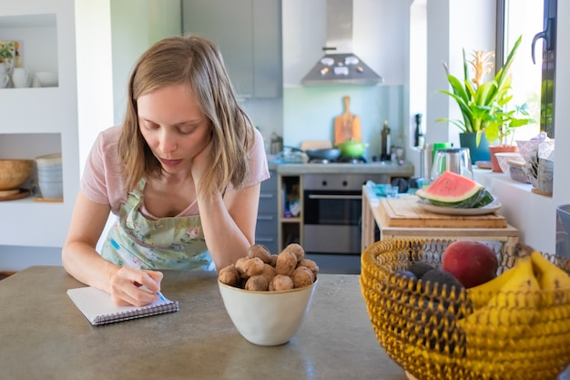 Focused housewife planning weekly menu in her kitchen, writing down grocery list in notebook. cooking at home concept