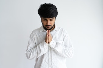Focused Indian man praying with his eyes closed and keeping hands together.
