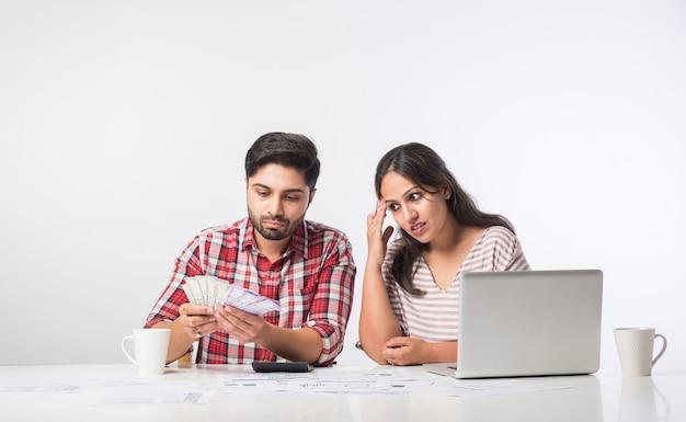 집중 인도 젊은 부부 회계, 청구서 계산, 온라인 뱅킹 서비스 및 계산기를 사용하여 계획 예산 논의, 재정 확인