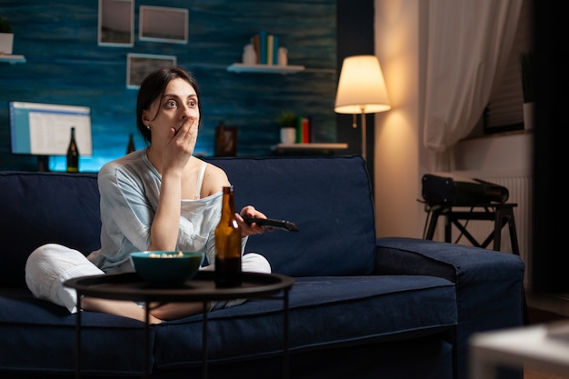 Focused interested woman eating popcorn watching interesting movie show