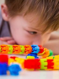 Сосредоточенный ребенок играет с красочной игрой