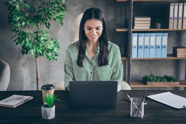 Сосредоточенная женщина-фрилансер сидит за столом в офисе, смотрит на экран ноутбука