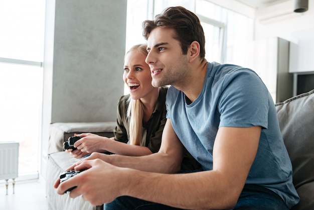 Focused lady and man playing video games at home in living room