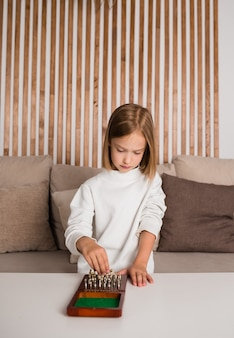 A focused little blonde girl is sitting on the sofa and playing chess at a table in the room