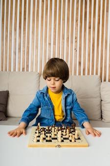 Сосредоточенный маленький мальчик сидит на диване и играет в шахматы в комнате