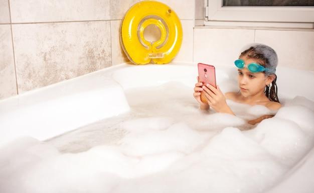 수영 고글에 집중된 어린 백인 소녀는 집에서 거품 욕조에서 목욕하는 동안 스마트 폰을 사용하여 셀카를 수행합니다. 코로나 바이러스 동안 어린이 및 가제트의 개념
