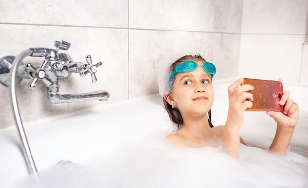 Сосредоточенная маленькая кавказская девушка в плавательных очках делает селфи с помощью смартфона