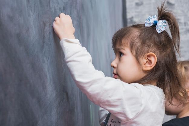 Focused little girl writing on blackboard