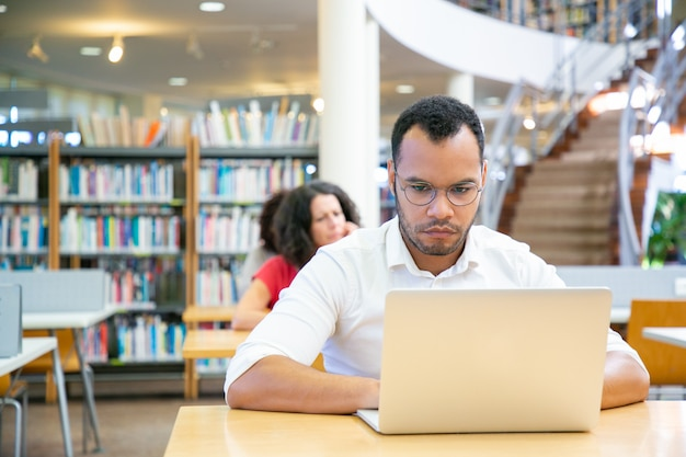Focused male adult student doing research in library