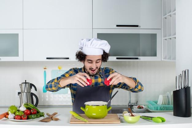 Cuoco unico maschio concentrato con verdure fresche che tengono peperoni rossi nella cucina bianca