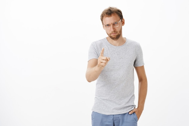 Focused male entrepreneur giving directions on duty being strict and serious with employees shaking index finger, pointing, dissatisfied or disappointed with bad work over white wall