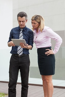 Focused male and female business people browsing on tablet computer outdoors.