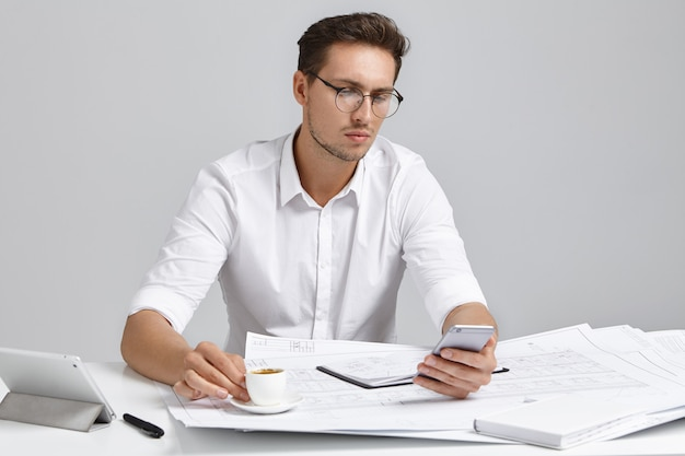 Focused male office worker uses smart phone for online communication, drinks espresso or cappuccino, sits at work place, has serious expression. young man works on architectual project alone