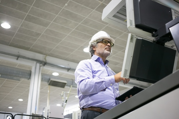 Focused male plant engineer in hardhat and glasses operating industrial machine, pushing buttons on control panel