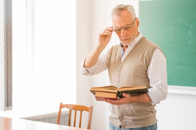 Focused male professor in glasses reading book in classroom