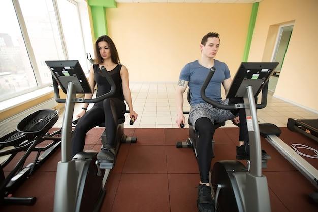 ジムでエアロバイクに焦点を当てた男性と女性