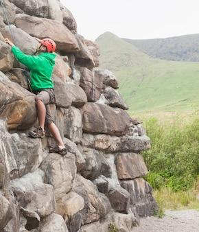 Focused man ascending a large rock face