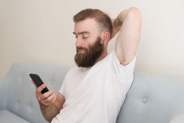 Focused man browsing on smartphone and sitting on sofa