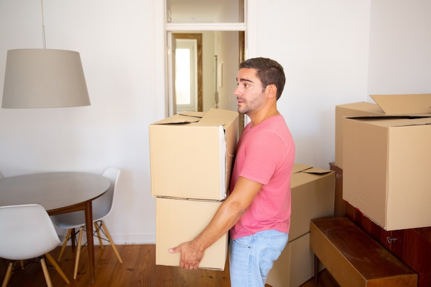 Focused man carrying carton boxes into new apartment, moving into new flat