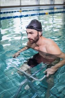 Focused man doing underwater bike in the pool