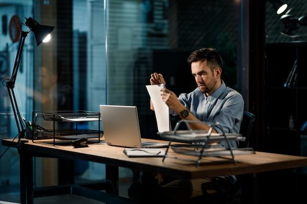 Сосредоточенный человек, закрепляющий документы скрепкой