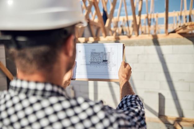 建物の計画で一枚の紙をよく見ているヘルメットをかぶった焦点を絞った男