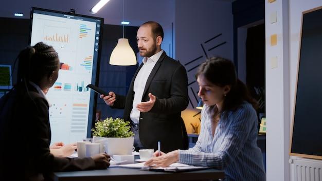 회사 회의실에서 일하는 모니터를 사용하여 관리 프로젝트를 설명하는 집중된 남자 리더