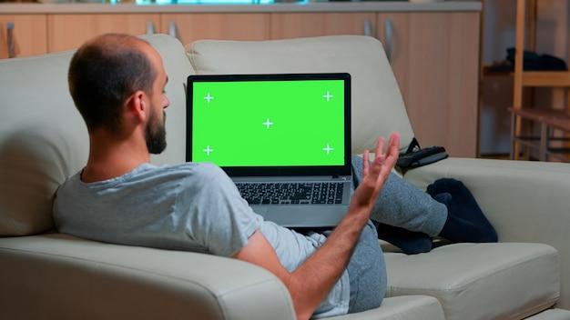 녹색 화면 크로마 키 디스플레이가 있는 노트북 컴퓨터를 보고 있는 집중된 남자